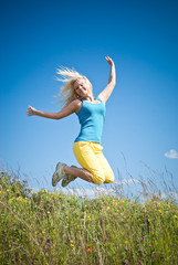 young woman jumping on   green meadow