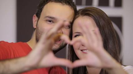 Happy couple making heart shape