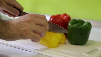 Male hand cuts pepper