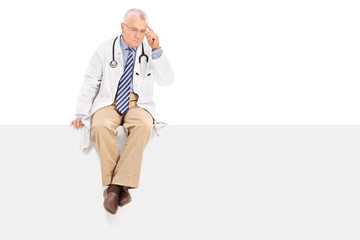 Pensive mature doctor sitting on a blank panel