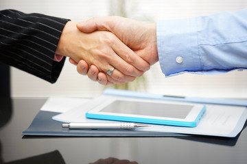 businessman and businesswoman are handshaking over documents and