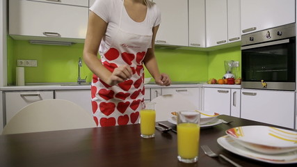 Girl in the kitchen puts freshly juice on the table