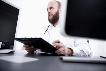 Arzt sitzt am Schreibtisch in seiner Praxis und unterschreibt