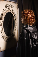 Very pretty woman vamp looking at her reflection in mirror