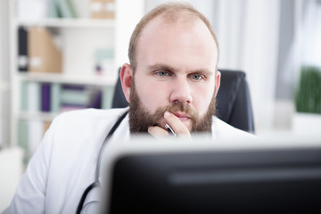 Arzt sitzt am Schreibtisch in seiner Praxis und arbeitet