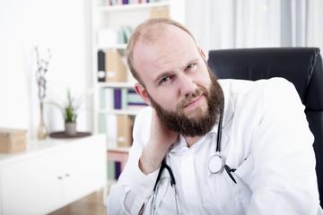 Arzt sitzt am Schreibtisch und hat Nackenschmerzen