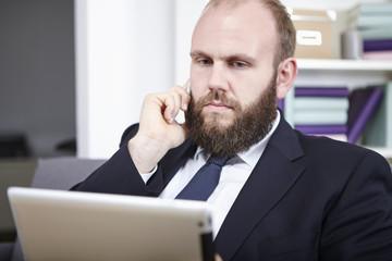 Geschäftsmann analysiert etwas auf seinem Tablett