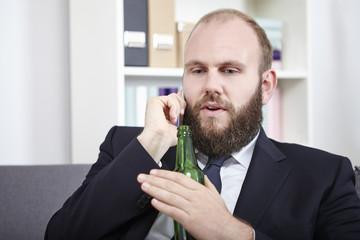 Geschäftsmann telefoniert mit seinem Handy und trinkt