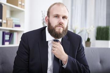 Portrait eines Geschäftsmann der seine Krawatte richtet