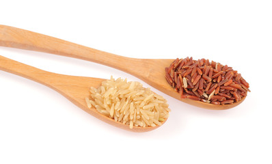 Red rice and brown rice in wooden spoon
