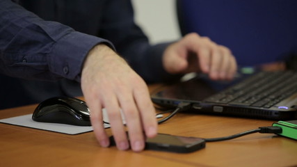 Male hands checking smartphone and working with laptop