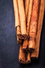 Bunch of cinnamon sticks close up on dark background with blank
