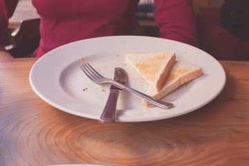 Woman leaving toast on her plate