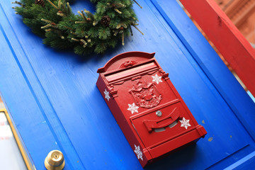 Red mailbox on the door for letters in Christmas
