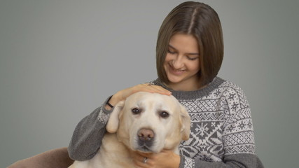 beautiful happy girl in a sweater hugging her beloved Labrador