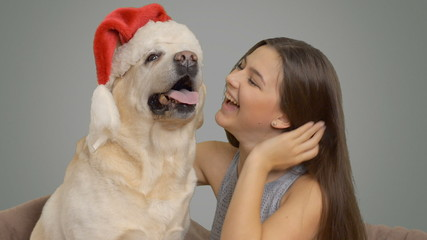 happy girl wears a hat of Santa Claus to his Labrador