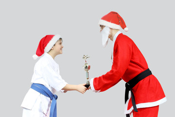 Sportsman receives from Santa Claus with a black belt karate Cup