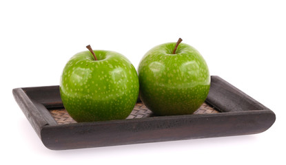 Green apple on wood tray