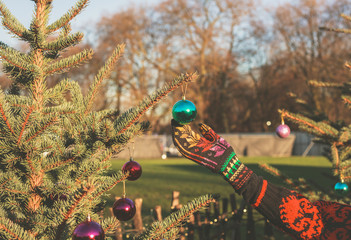 Hand touching bauble on christmas tree outside