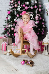 beautiful girl sitting on a rocking horse near a Christmas tree