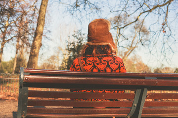 Woman in winter hat sitting on bench