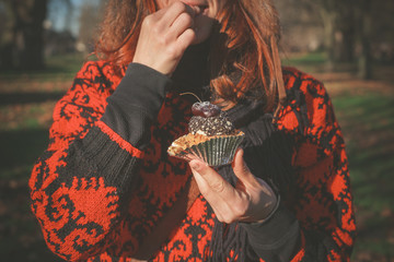 Woman in park with cupcake
