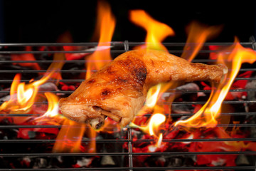 Grilled chicken Legs with flames on the grill