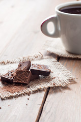 cup coffee with chocolat on wooden table and black background