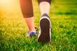 Leinwanddruck Bild - Girl running shoes closeup, green grass, woman fitness