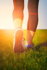 Girl running shoes closeup, green grass, woman fitness