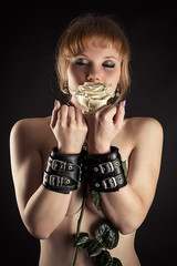 beautiful woman slave in handcuffs with flower in hand