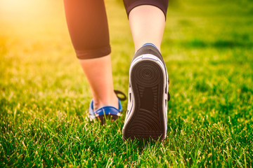 Girl running shoes closeup, green grass, woman fitness