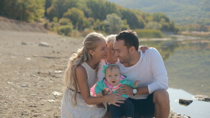 Happy family filled with love sitting on a background of lake