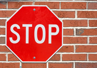 Bright stop sign on a red brick background