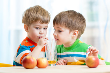 brothers kids drink juice together from single glass