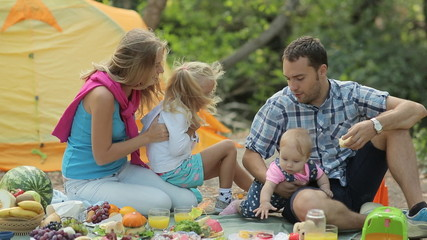 Young parents with two lovely daughters rest in the forest in