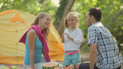 Cute little blonde girl with parents outdoors with watermelon
