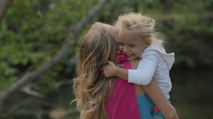 Full of energy mom holds on hands her little girl