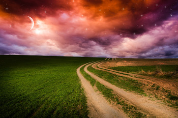 Dirt road and rainbow in the night.