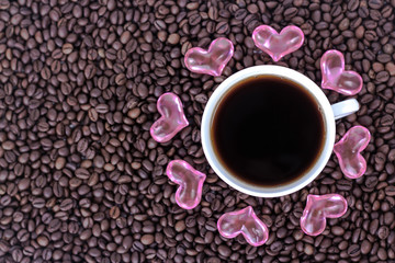 cup of coffee with hearts on the background of coffee beans