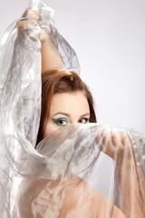 Frau mit markantem Makeup verhüllt ihr Gesicht