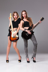 Two beautiful girls playing guitars