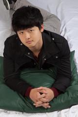 Asian man reclining and thinking