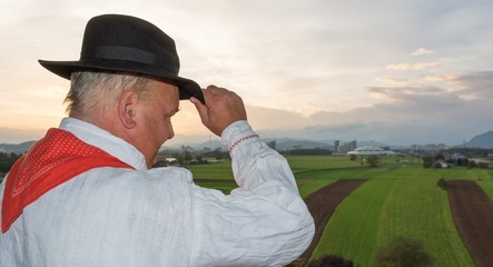 Man wearing traditional clothing looking at fields