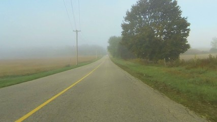Point of view drive down a country road through fog