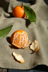 Juicy ripe tangerines with leaves on tablecloth