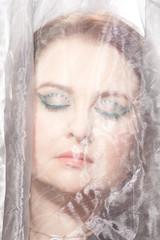 Glamourös geschminktes Gesicht hinter einem Schleier