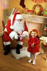 Santa Claus giving  present to  little cute girl near