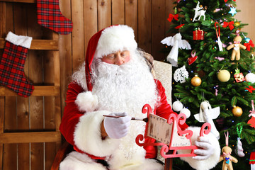 Santa Claus sitting in comfortable rocking chair and decorated