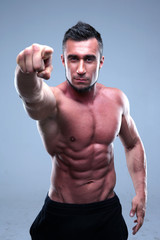 Muscular man pointing at the camera